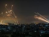 Tên lửa của Hamas phóng từ Dải Gaza (phải) và hệ thống Vòm Sắt phóng tên lửa đánh chặn (trái). Ảnh: AFP.