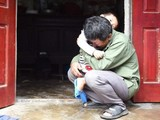 ông Lê Văn Tuấn ôm đứa cháu trai, bật khóc khi không có tin tức gì về người con trai Lê Văn Hà (ảnh: Getty Images)