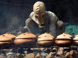 Anh Bùi Văn Cường đeo mặt nạ phòng độc để kho cá trắm (ảnh: Reuters)
