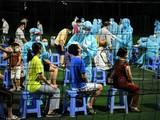 Lấy mẫu xét nghiệm tại một sân banh trên địa bàn phường 15, quận Gò Vấp, trong đêm. Ảnh: Lan Chi