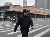 Một sĩ quan cảnh sát tuần tra ở chợ hải sản Huanan, Vũ Hán nơi mà các nhà khoa học tin là khởi điểm của dịch bệnh (Ảnh: Washington Post)