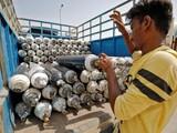 Một tài xế chất các bình oxy lên xe tải chuẩn bị chở tới các bệnh viện để hỗ trợ điều trị bệnh nhân COVID-19 (Ảnh: Reuters)