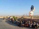 Các binh sĩ Afghanistan ngồi bên một cây cầu gần biên giới với Tajiskistan hồi tháng 6/2021 (Ảnh: AP)
