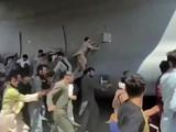 Hình ảnh kịch tính cho thấy nhiều người Afghanistan cố bám víu lấy chiếc máy bay quân sự Mỹ ở sân bay Kabul (Ảnh: AP)