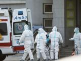 Nhân viên y tế chuyển bệnh nhân đến bệnh viện để điều trị tại thành phố Vũ Hán. Ảnh: EPA-EF