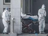 Các nhân viên y tế đưa bệnh nhân vào bệnh viện tại Trung Quốc. Ảnh: AFP