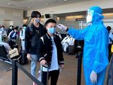 Nhân viên y tế kiểm tra nhiệt độ của hành khách ở sân bay (Ảnh - BYT)