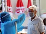 Nhân viên y tế kiểm tra nhiệt độ cho người dân (Ảnh - BYT)