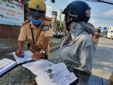 Một người phụ nữ bị CSGT phạt vì mang giấy tờ xe photo dù có chứng thực. Ảnh: Thanh Niên