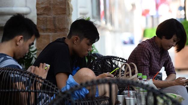 """Việc khách hàng thích """"chơi"""" với smartphone đã làm các chủ quán cà phê nhỏ thất thu khá nặng nề."""