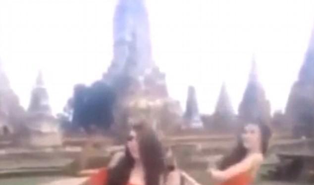 Hai phụ nữ mặc váy cam ngắn cũn nhảy nhót trước đền thiêng