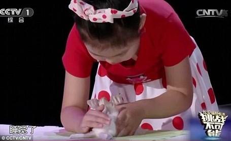 Cô bé Han Jiaying, 5 tuổi, đang thể hiện khả năng thôi miên động vật trong chương trình truyền hình thực tế tìm kiếm tài năng của Trung Quốc.