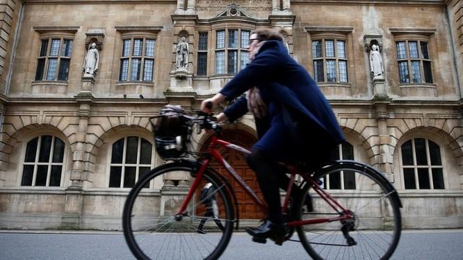 Một người phụ nữ đi xe đạp bên cạnh trường Oriel College ở Oxford, Anh (ảnh: Thomson Reuters)