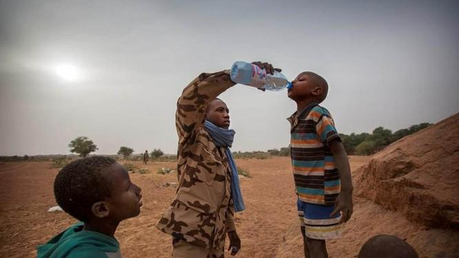 Một thành viên của đội MINUSMA Chadian cung cấp nước cho một cậu bé ở Kidal, Mali ngày 17.12.2016. Ảnh: Reuters