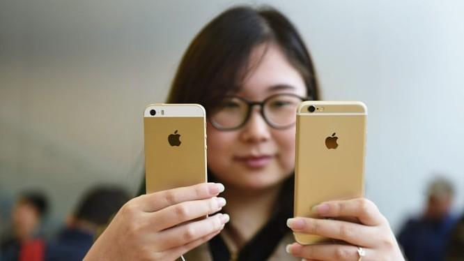 Một khách hàng đang so sánh iPhone SE và iPhone 6S tại một cửa hàng của Apple. Ảnh: CNBC