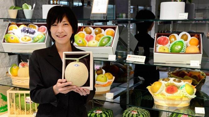Miyuki Kaida, nhân viên chuỗi cửa hàng hoa quả Sun Fruits, giới thiệu hoa quả cao cấp tại một cửa hàng tại Tokyo. Ảnh: AFP