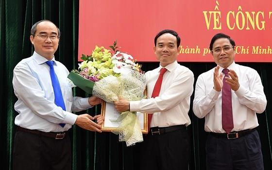 Bí thư Thành ủy TP.HCM Nguyễn Thiện Nhân (ngoài cùng, bên trái) tặng hoa chúc mừng tân Phó Bí thư Thường trực Thành ủy TPHCM Trần Lưu Quang (ở giữa) - Ảnh: SGGP