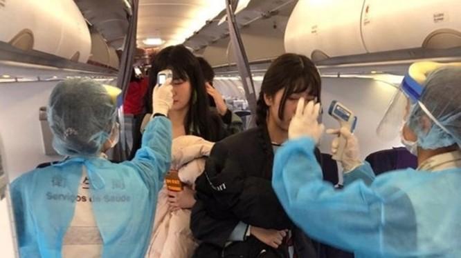 Đề phòng dịch bệnh lây lan, các nhân viên y tế sân bay Ma Cao lên máy bay đo thân nhiệt mọi hành khách trên chuyến bay từ Vũ Hán đến. (Ảnh: Đông Phương).