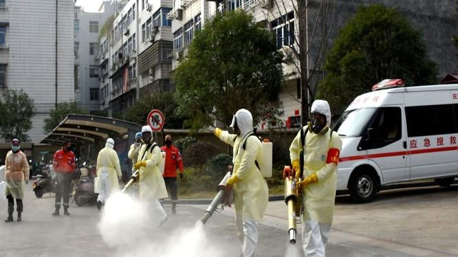 Các nhân viên y tế phun thuốc khử trùng trong các khu dân cư Vũ Hán (Ảnh: Reuters).