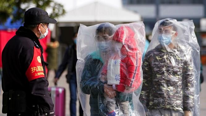 Ngày 10/2 nhiều địa phương, người nghỉ Tết đã quay về các thành phố. Hành khách ở ga Thượng Hải sử dụng phương tiện phòng hộ tự chế. (Ảnh: Reuters)