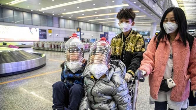 Hành khách ở Quảng Châu tự tạo mặt nạ phòng hộ bằng vỏ thùng đựng dầu ăn (Ảnh: EPA)