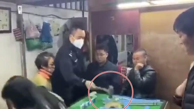 Người cảnh sát giận dữ dùng búa đập phá bàn mạt chược (Ảnh: Đông Phương)