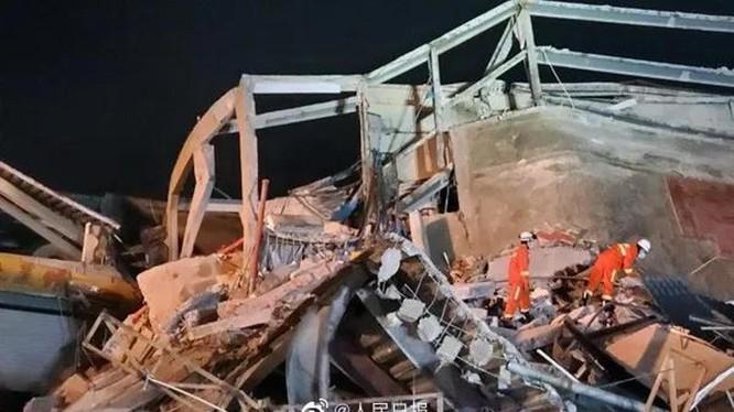 Các nhân viên cứu hộ tìm kiếm nạn nhân trong đống đổ nát (Ảnh: Nhân dân Nhật báo).