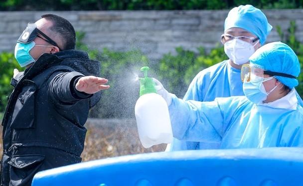 Nhân viên y tế ở Vũ Hán khử trùng bệnh nhân trước khi ra viện.(Ảnh Đông Phương).