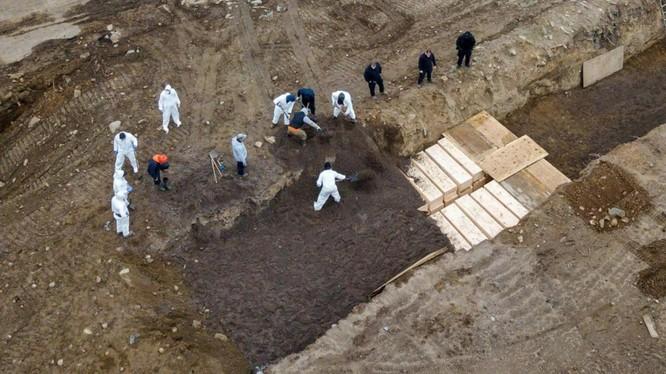 Hình ảnh các tù nhân được trưng dụng để chôn xác những nạn nhân của dịch bệnh COVID-19 trong các nấm mồ tập thể trên đảo Hart (Ảnh: Reuters).