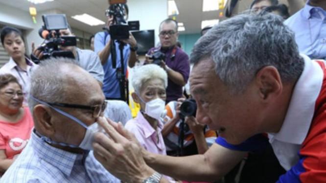 Do dịch bệnh bùng phát trở lại, Singapore ban hành lệnh bắt buộc người ra đường phải đeo khẩu trang. Trong ảnh: Thủ tướng Lý Hiển Long đeo khẩu trang cho người dân (Ảnh: Guancha).