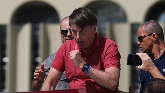 Tổng thống Jair Bolsonaro không đeo khẩu trang ho khi phát biểu trước những người biểu tình phản đối phong tỏa chống dịch (Ảnh: Voorp).