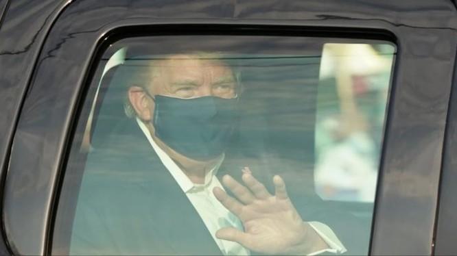 Ông Trump ngồi trên xe vẫy chào những người biểu tình ủng hộ sau cửa kính (Ảnh: The Australian).