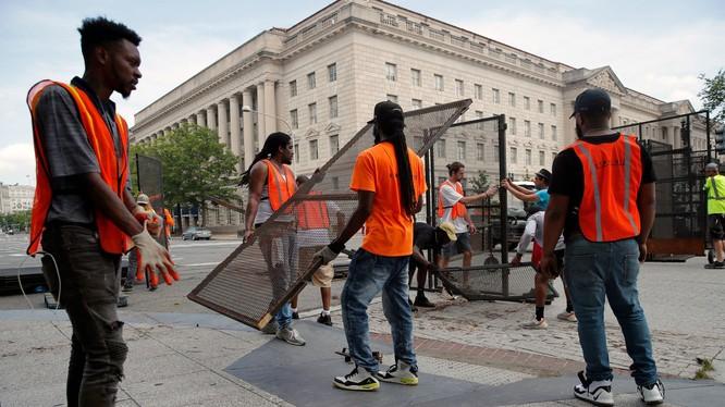 Các nhân viên công tác khẩn casaps dựng hàng rào lưới thép bảo vệ xung quanh Nhà Trắng (Ảnh: Reuters).