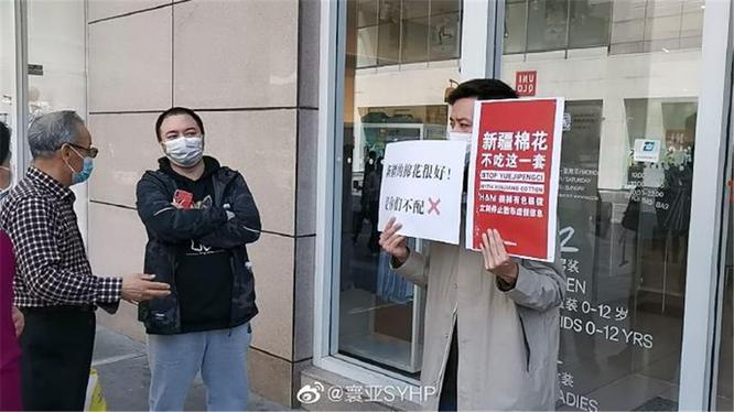 Một người mang biểu ngữ tẩy chay H&M đứng chắn trước một cửa hàng của thương hiệu này ở Hồ Nam (Ảnh: Đa Chiều).