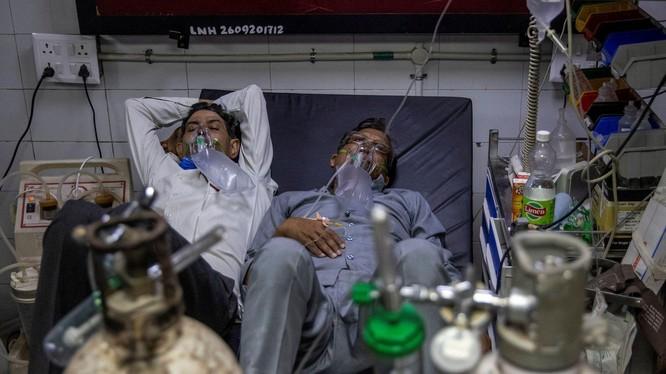 Số bệnh nhân liên tục gia tăng đã khiến nguồn lực y tế cạn kiệt. Trong ảnh: 2 bệnh nhân COVID-19 nằm chung một giường trong một bệnh viện ở Delhi (Ảnh: Reuters).