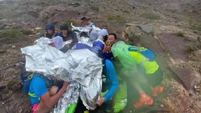 Các vận động viên ôm nhau truyền nhiệt sưởi ấm khi bị mưa đá, gió lạnh (Ảnh: toutiao).