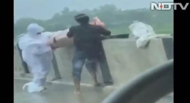 Hình ảnh một nhân viên y tế và người nhà ném thi thể bệnh nhân COVID-19 xuống sông trên NDTV (Ảnh: Chinatimes).