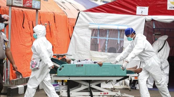 Các bác sĩ đưa bệnh nhận nặng từ lều tạm vào phòng điều trị đặc biệt (Ảnh: Reuters).