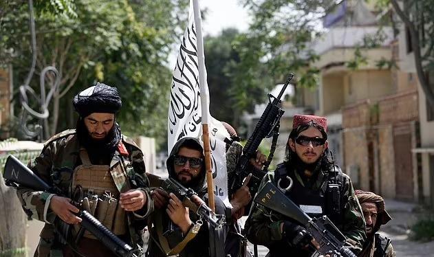Lính Taliban mang quốc kỳ mới đi tuần trên đường phố Kabul hôm 19/8 (Ảnh: Dailymail).