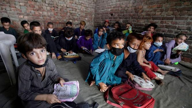 Trẻ em Afghanistan theo bố mẹ chạy sang Pakistan tị nạn (Ảnh Reuters).