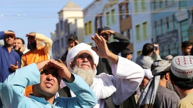 Dân chúng xem thi thể bị Taliban treo lên thị chúng ở thành phố Herat (Ảnh AP).