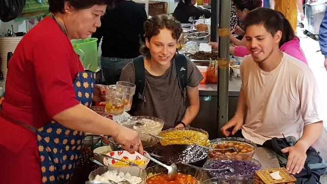 Du khách nước ngoài thích thú thưởng thức các món ăn tại ngõ Đồng Xuân