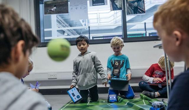 Các em học sinh thực hành cùng robot trong một giờ học