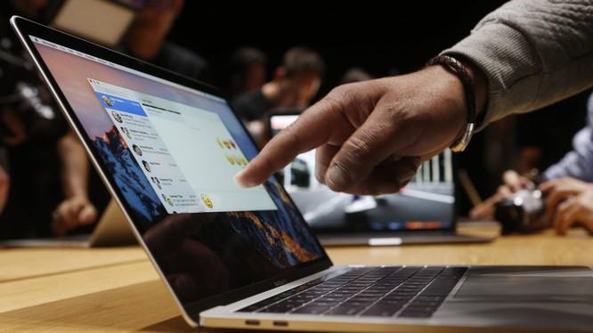 Một vị khách đang chỉ tay vào chiếc MacBook Pro tại sự kiện của Appleở Cupertino. Ảnh Reuters/Beck Diefenbach