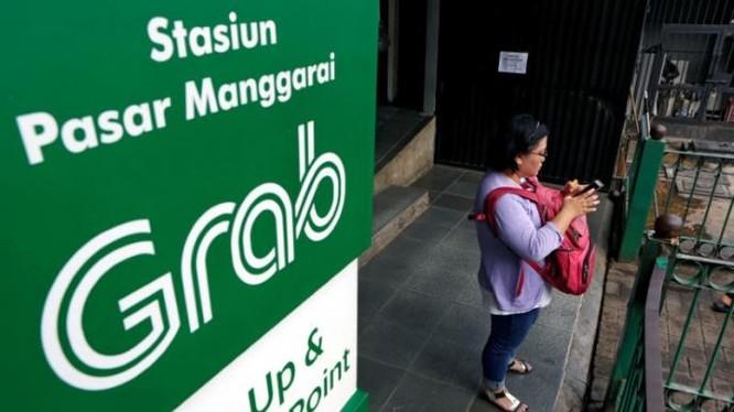 Một phụ nữ dùng ĐTDĐ gọi xe của hãng Grab tại Jakarta