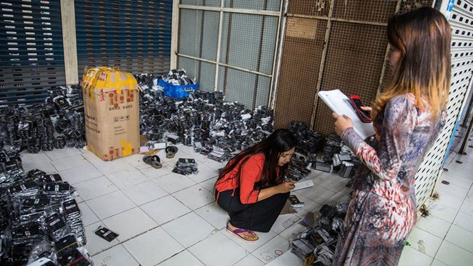 Nhân viên đang kiểm kê phụ kiện điện thoại di động tại một cửa hàng ở Yangon ẢNH: BLOOMBERG