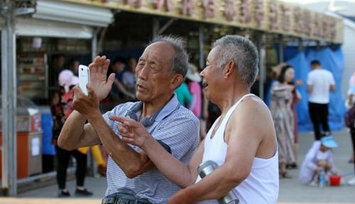 Hai người cao niên đang sử dụng điện thoại di động ở tỉnh Sơn Đông, tháng 5/2017. Ảnh: VCG.