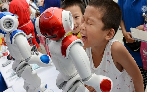 Những em bé đang nô đùa với robot trong một triển lãm ở Trung Quốc - Ảnh: Business Insider.
