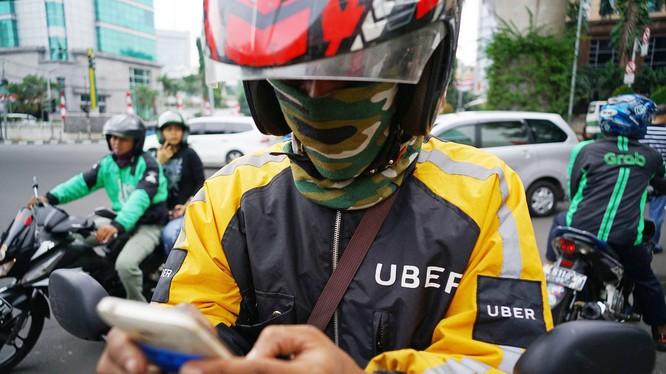 Jakarta, Indonesia: Một lái xe ôm Uber đang kiểm tra smartphone của mình, trong khi lái xe Go-Jek thì chở khách, phía bên phải là một xe ôm Grab. Ảnh: Straitstimes.com