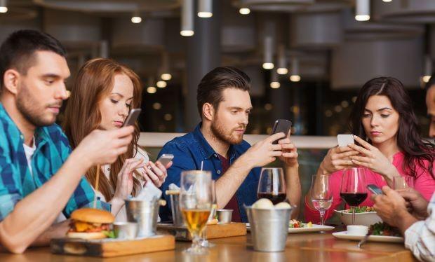 Cảnh tượng quen thuộc: Ngồi cạnh nhau nhưng mỗi người đều chỉ nhìn vào màn hình điện thoại. Dreamstime/TNS